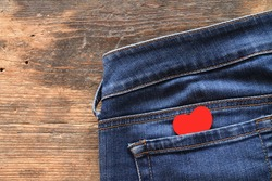 Small red heart in jeans pocket on wooden table