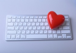 Small red heart on keyboard. Internet dating concept