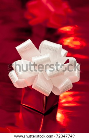 Small red present with white bow. Red background