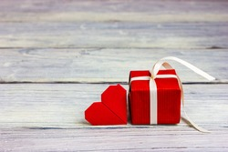 Small red valentine's day gift with a note in the shape of a red heart. Congratulations to your loved one on February 14.