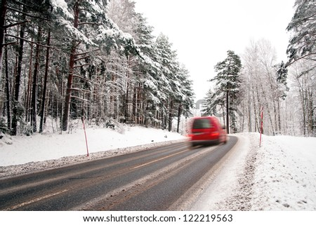 Small red van in blurred motion on country road in winter