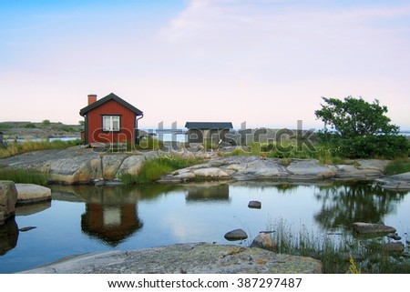 Small red wooden hut on a rocky skerry in the outer archipelago of Stockholm, Sweden. Grass in front and reflections in a small pond of water in front of the house. #387297487