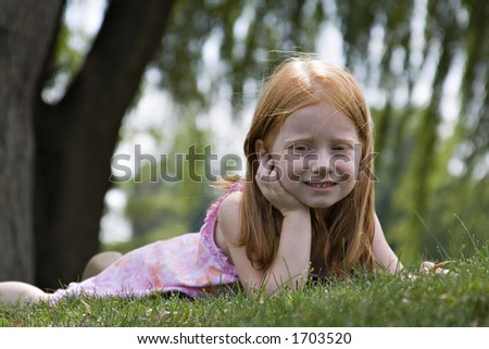 Small redheaded girl laying in grass contemplating the world around her.