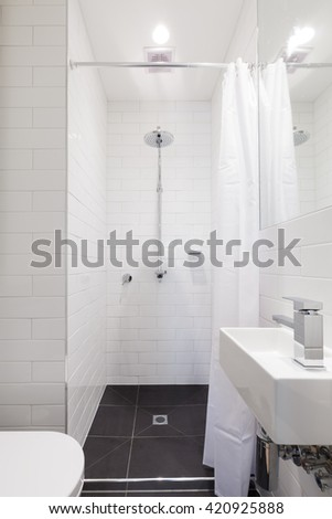 Small renovated white ensuite bathroom with rain shower #420925888
