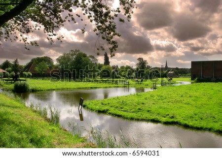 Small river and green fields in famous Zaanse Schans village near Amsterdam, Netherlands.