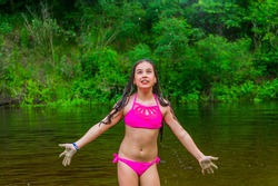 small river. Teenage girl enjoys the warm weather during the summer holidays. Teenage girl bathes
