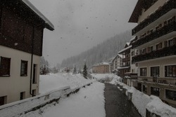 Small river Torrente Frigidolfo in the village of Santa Caterina in heavy snowfall. Visible hotels and houses with some snow flakes falling down.