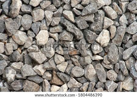 Photo of  small road stone background, dark gravel pebbles stone texture. Closeup top view gravel. Gravel in garden. Pattern.