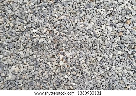 Photo of  small road stone background, dark gravel pebbles stone texture seamless texture