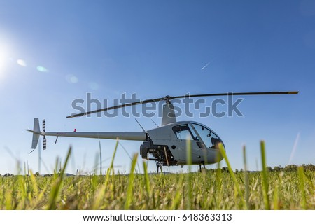 Small Robinson R22 light utility helicopter parked on grass airport. One of the world's most popular light helicopters with twin blades and a single engine Photo stock ©