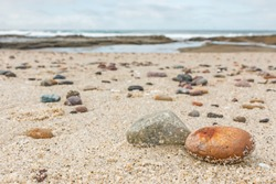 Small rocks scattered on beach sand close up.Shallow depth of field.Selective focus on foreground rocks.Blurred background of multicolor stones of different shapes and sizes,ocean waves,overcast sky