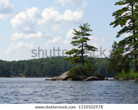 Small rocky island with a green pine surrounded with blue water and green forest mountains under blue sky and white clouds.Philippe Lake.Gatineau Park Quebec                                #1150502978