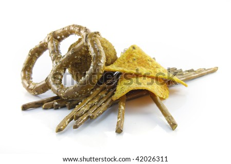Small round scotch egg with salty pretzels and nachos on a reflective white background