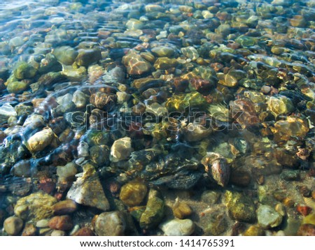 Small round stones under clear clear water. Beautiful pattern of multi-colored pebbles in the river.