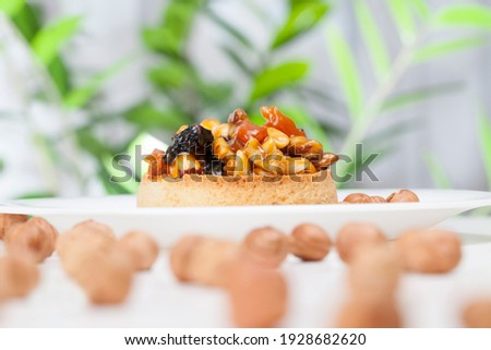 small round tartlet with a variety of fillings, crispy tartlet with hazelnuts, peanuts and other ingredients, dough tartlet nuts and dried fruits covered with caramel