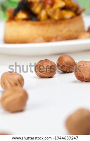 small round tartlet with a variety of fillings, crispy tartlet with hazelnuts, peanuts and other ingredients, tartlet made of dough nuts and dried fruits covered with caramel