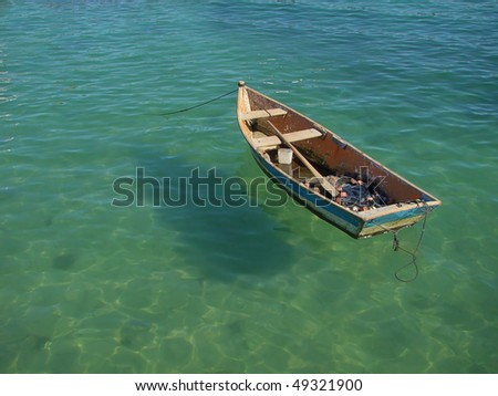 small row boat floating on clear water