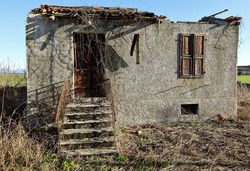 Small ruined house isolated and abandoned in the countryside, with entry stair and concrete facade. Dry grass around it.