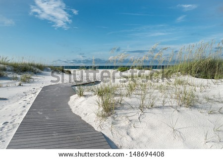 Small rustic boardwalk footpath through snow white sand dunes at a pristine Florida beach.