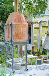 Small rusty metal incinerator stove in summer outdoor study. Old oven and chair with white dust or ash on outdoor in summer handicraft workshop