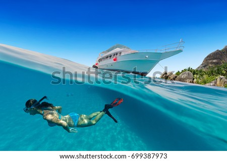 Small safari boat with snorkeling woman underwater. Beautiful split shot under and above water. Travel lifestyle, water sport outdoor activities, swimming and snorkeling #699387973
