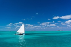 Small sailboat moves through clear and calm waters near Hope Town, Abaco, Bahamas