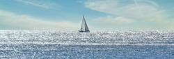 Small sailboat sailing through a silver sea in a sunny day