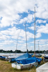 Small sailing or fishing boats on land with masts and covers on in Mudeford Quay, southern England, beautiful blue cloudy sky, many dingies stored on dry shore