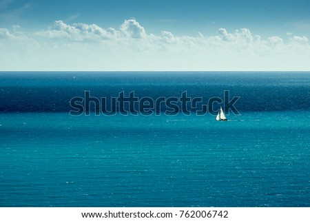 small sailing yacht alone on the beautiful blue expansive calm sea off the french riviera coast #762006742
