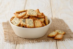 Small salty rectangular crackers with poppy and sesame seeds in a beige ceramic bowl on a white wood table. Crispy wheat flour snack and beer appetizer. Front view.