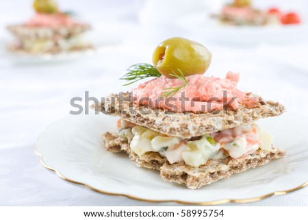Small sandwiches for catering event on white plate and table cloth
