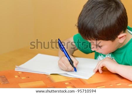 small school boy writing homework from school in workbook