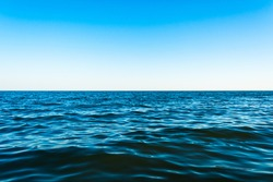 Small sea waves against the blue sky and white horizon