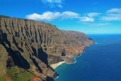Small secluded beach surrounded by sea and cliffs at the Na Pali Coast, spectacular aerial view shot from a helicopter, Kauai, Hawaii