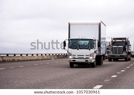 Small semi truck fleet with box trailer and big rig classic semi truck fleet running on wide highway with traffic left behind