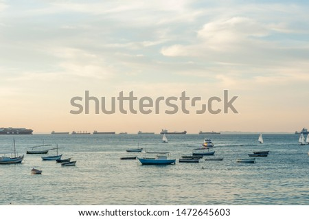 Small Ships / boats with vessels / cargo ships / container ships in the back in a calm sea at evening in Salvador de  Bahia, Brazil #1472645603