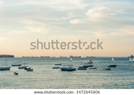 Small Ships / boats with vessels / cargo ships / container ships in the back in a calm sea at evening in Salvador de  Bahia, Brazil #1472645606