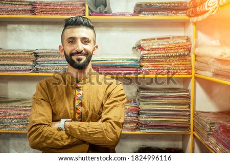 small shop owner indian man selling shawls at his store