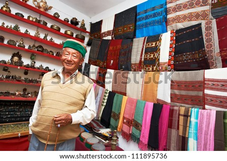small shop owner indian man selling shawls, clothing and souvenirs at