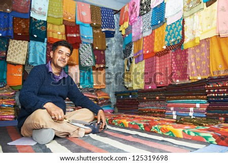 indian man selling shawls, clothing and souvenirs at his store - stock