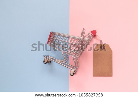 Small shopping cart with blank price tag on pastel background minimal creative concept