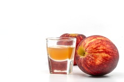 Small Shot Glass of organic Apple Cider Vinegar with the mother, two red apples is aside of the glass, image on white background.