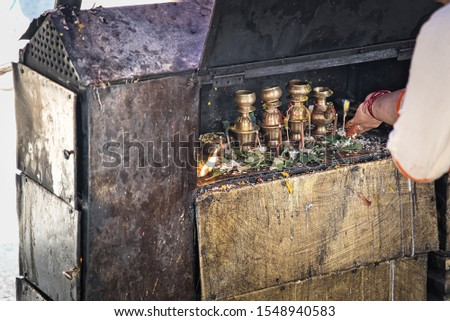 Small shrine of black and white brass for inductive prayers with flower petals and offerings with the hand of a parishioner offering. Nepal. Asia.