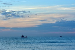Small silhouette of a fishing boat against a sunset background