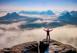 Small silhouette of hiker man enjoying beautiful sunrise in morning mountains. Traveler with raised hands standing on mountain with white fog below.