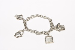 Small silver charm bracelet with 4 charms isolated against white background.