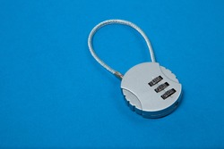 Small silver iron cipher lock with a coded set on blue background