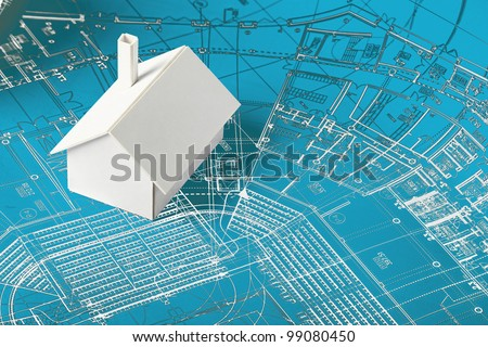 Small simple white model house on blueprints