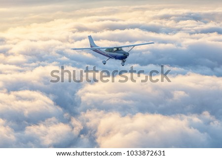 Small single engine airplane flying in the gorgeous sunset sky #1033872631