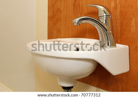 Small sink with wood panel and yellow wall